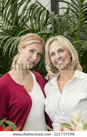 Portrait of happy mother and daughter in greenhouse