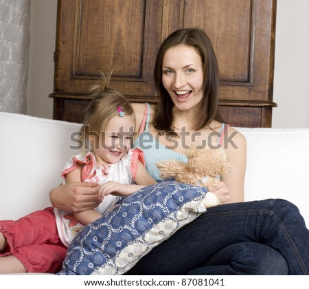 portrait of happy mother and daughter on sofa, smiling hugging