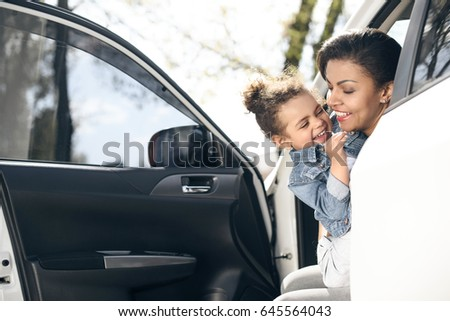 portrait of happy mother and daughter sitting in car on parking