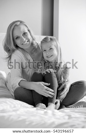 Portrait of happy mother and daughter sitting on bed at home
