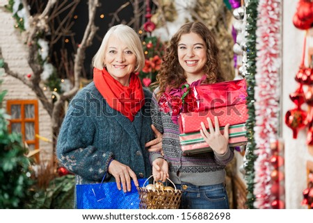 Portrait of happy mother and daughter with Christmas presents standing together at store - stock photo