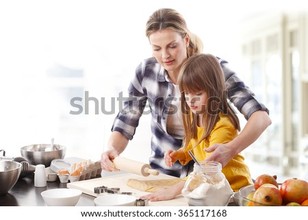Portrait of happy mother and her cutie daughter cooking together in the kitchen.