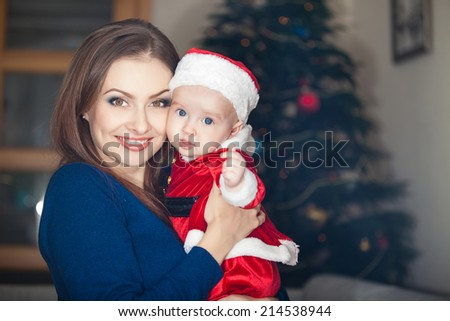 Portrait of happy mother and little baby in suit of santa's helper