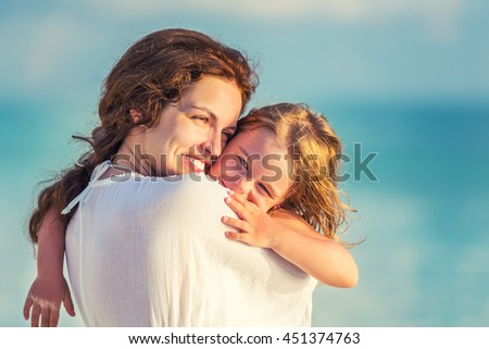 Portrait of happy mother and little daughter on sunny beach