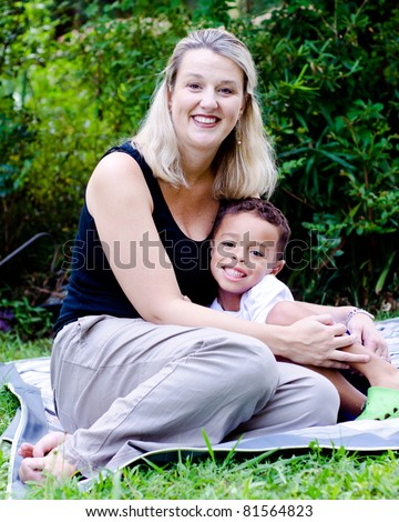Portrait of happy mother and mixed race son outdoors at park - stock photo