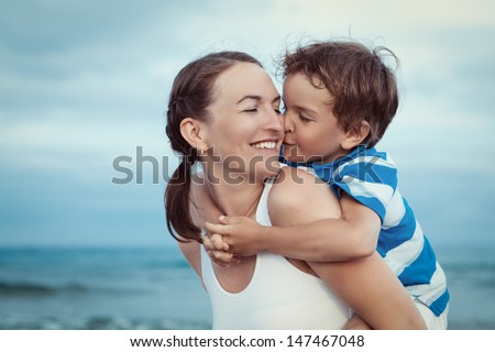 Portrait of happy mother and son at sea, outdoor - stock photo