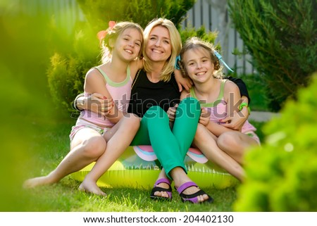 Portrait of happy mother and two daughters sisters twins in the summer garden of his country house. Photo shows a cheerful smile on the faces of people having a rest. - stock photo