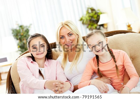 Portrait of happy mother and two daughters sitting on sofa
