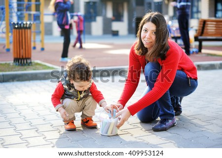 Portrait of happy mother drawing with chalks with her toddler son outdoors near the playground - stock photo