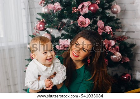 Portrait of happy mother in a santa's hat and little baby in santa's suit on the Chrismas