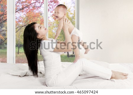 Portrait of happy mother playing with her baby on the bedroom at home in autumn season