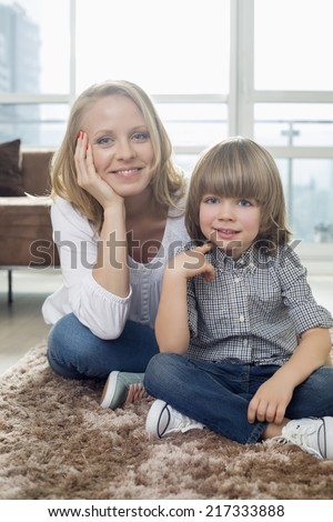 Portrait of happy mother sitting with boy on rug in living room - stock photo