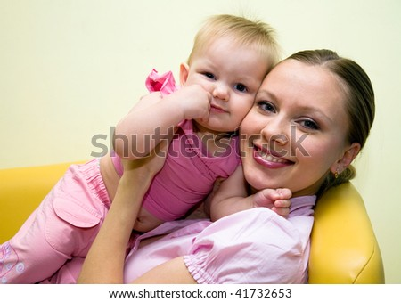 Portrait of happy mother with beautiful baby on the yellow sofa