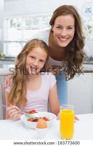 Portrait of happy mother with daughter having breakfast in the kitchen at home