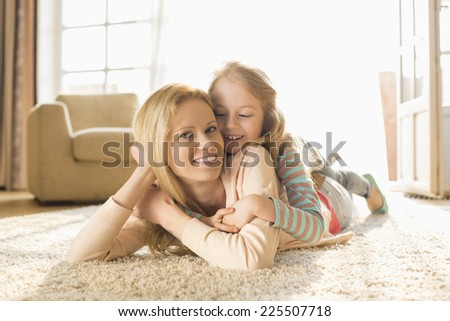 Portrait of happy mother with daughter lying on floor at home - stock photo