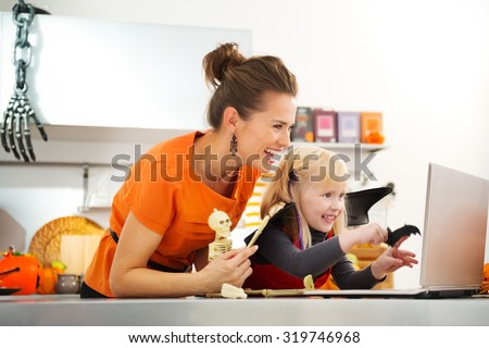 Portrait of happy mother with halloween dressed daughter having video chat on laptop with friends in decorated kitchen. Traditional autumn holiday - stock photo