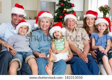Portrait of happy multgeneration family in Santa hats celebrating Christmas at home - stock photo