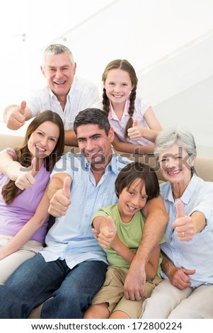 Portrait of happy multi-generation family gesturing thumbs up at home - stock photo