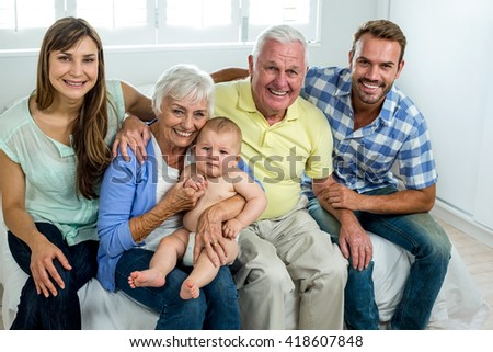 Portrait of happy multi-generation family on bed at home - stock photo