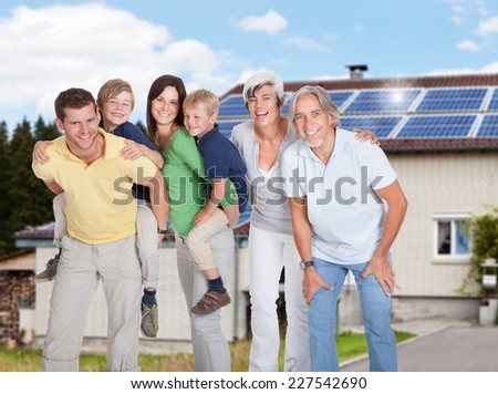 Portrait of happy multi generation family standing against home - stock photo