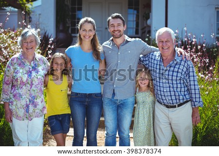 Portrait of happy multi-generation family standing against house - stock photo