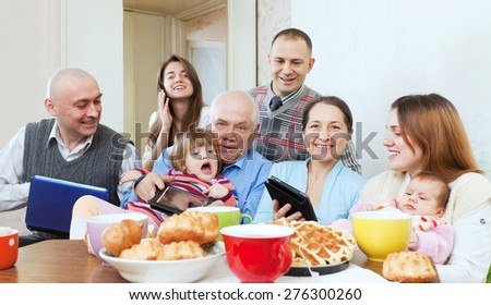 Portrait of happy multigeneration family or group of friends posing together with various electronic communication devices over tea  at home - stock photo