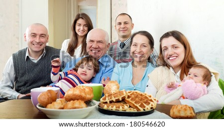 Portrait of happy multigeneration family posing together over tea at home interior - stock photo