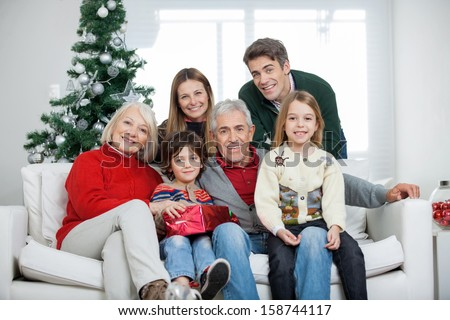 Portrait of happy multigeneration family with Christmas present in house