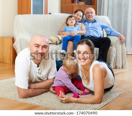 Portrait of happy multigeneration family with little children at floor in home