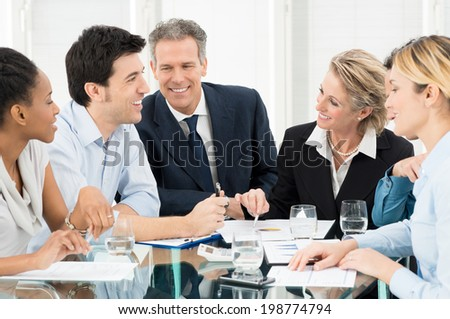 Portrait Of Happy Multiracial Businesspeople Discussing In Meeting - stock photo