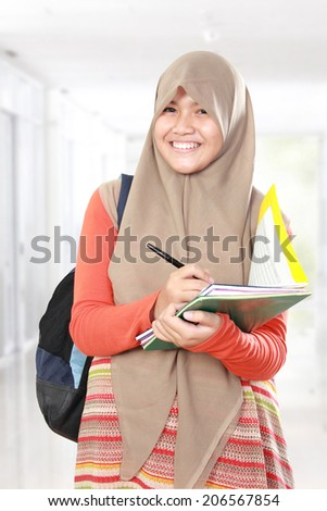 Portrait of happy muslim kid student writing something on book - stock photo