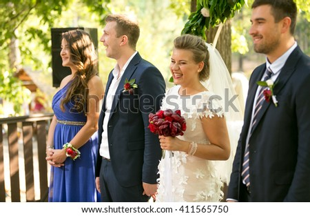 Portrait of happy newly married couple and guests at wedding ceremony - stock photo