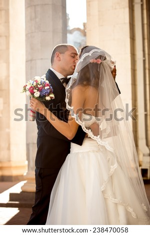 Portrait of happy newly married couple kissing on street at sunny day - stock photo