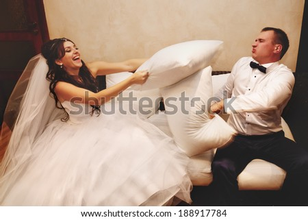 Portrait of happy newlywed couple fighting with pillows on sofa - stock photo