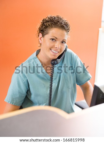 Portrait of happy nurse answering telephone while working at hospital reception - stock photo