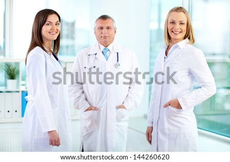 Portrait of happy nurses looking at camera with mature doctor behind - stock photo