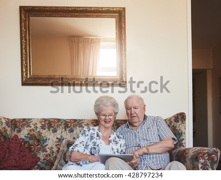 Portrait of happy old couple sitting together at home on sofa and using digital tablet. Elderly man and woman using touchscreen computer at old age home. - stock photo