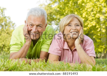 Portrait of happy old people lying on green grass.