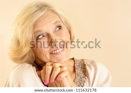 portrait of happy older woman on a beige background