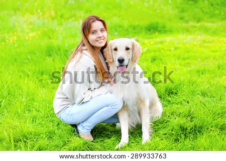 Portrait of happy owner and Golden Retriever dog together on the grass in sunny summer day