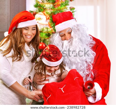 Portrait of happy parent congratulate little daughter with New Year holidays, Santa Claus with big red gift bag, wintertime concept - stock photo