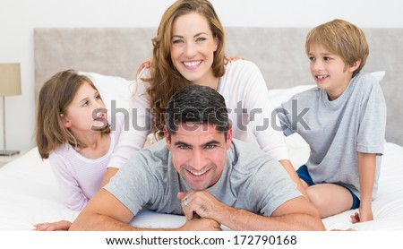 Portrait of happy parents and children in bed