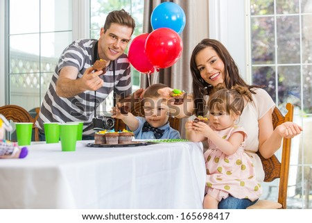 Portrait of happy parents and children showing cupcakes at birthday party