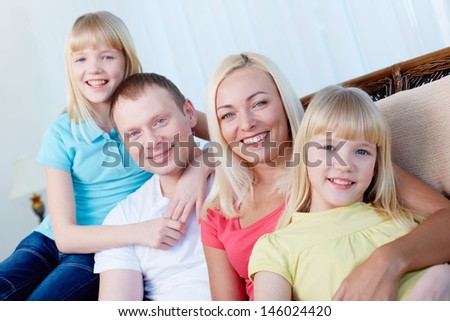 Portrait of happy parents and children sitting in a row - stock photo