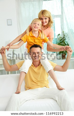 Portrait of happy parents and their cute daughter spending leisure at home