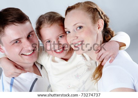 Portrait of happy parents and their daughter in studio