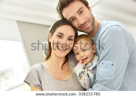 Portrait of happy parents holding baby girl  - stock photo