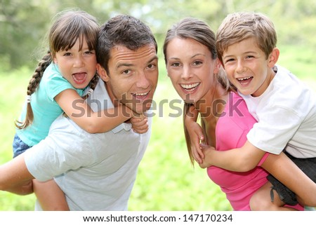 Portrait of happy parents holding kids on their back - stock photo