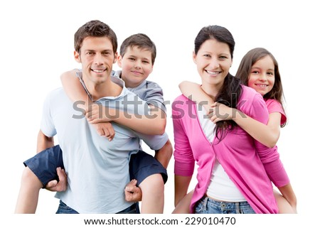 Portrait of happy parents piggybacking children against white background - stock photo