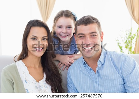Portrait of happy parents with daughter at home